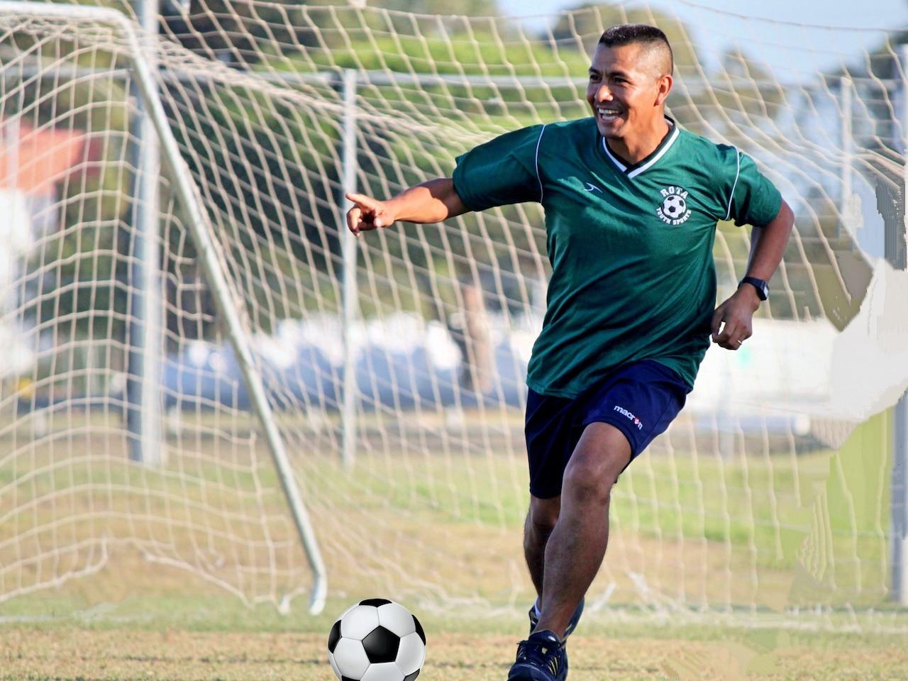 A man dressed in a soccer uniform runs toward a soccer ball on a field.