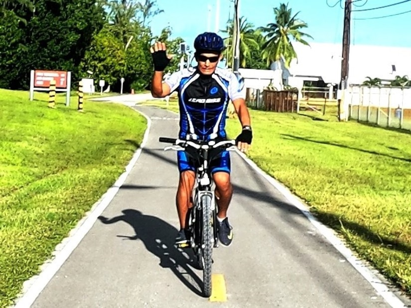 A man wearing a bicycle helmet and gear rides a bike on a path.