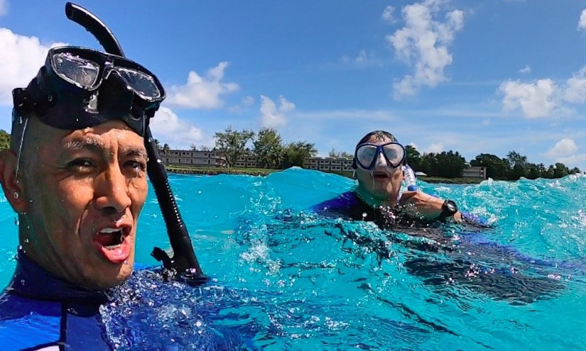 Two people snorkel in clear, blue water with the shoreline in the background.