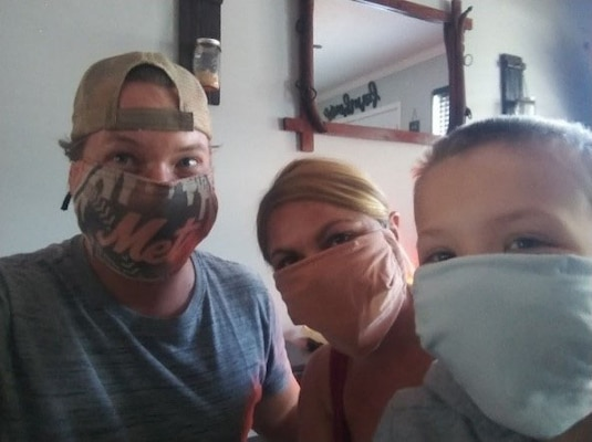 Employee poses with contest winning face covering