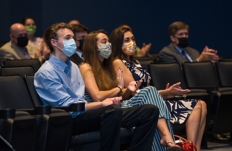 Donned in protective facial masks in the wake of the coronavirus pandemic, Gina Hartman (right) and her children Logan (left) and Sofia (center), applaud during the Air Force Technical Applications Center's Change of Command ceremony June 30, 2020.  Gina's husband, Col. Chad Hartman, relinquished command of the nuclear treaty monitoring center to Col. Katharine Barber at Patrick AFB, Fla., as others from the center are seen in background adhering to social distancing requirements.  (U.S. Air Force photo by Amanda Ryrholm)