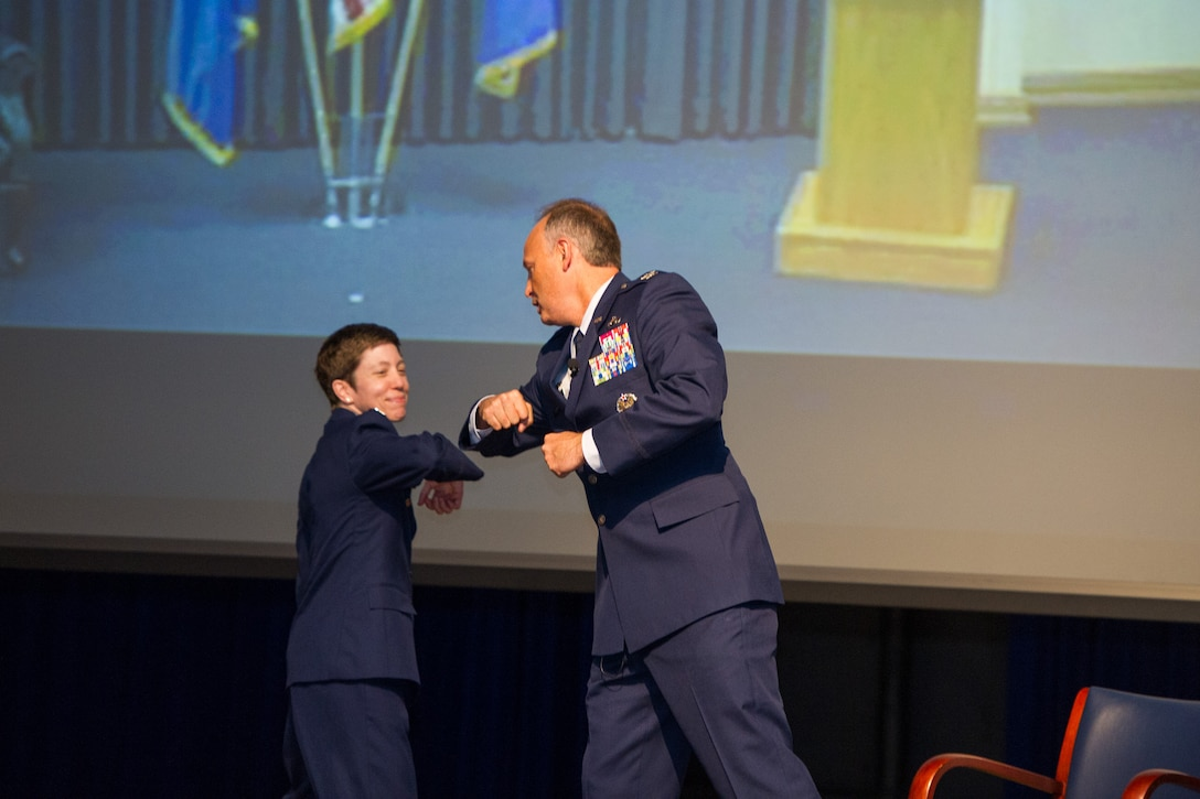 To avoid direct contact due to the coronavirus pandemic, incoming commander Col. Katharine Barber (left) bumps elbows with outgoing commander Col. Chad Hartman (right) in place of a handshake during the Air Force Technical Applications Center's Change of Command ceremony June 30, 2020.  (U.S. Air Force photo by Amanda Ryrholm)