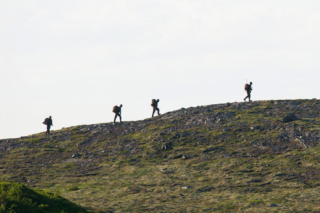 Marines hike up a mountain.