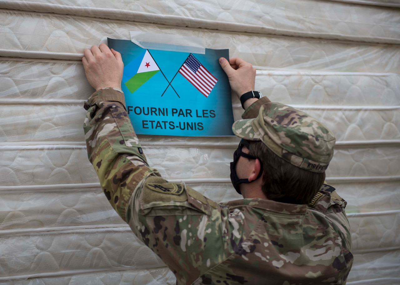 A soldier hangs a sign that bears the flags of the United States and DJibouti.
