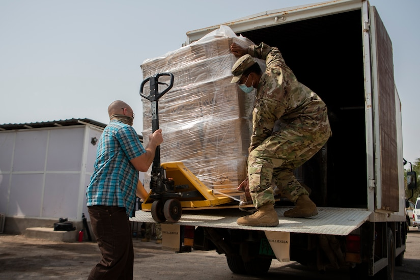 Two soldiers — one in civilian clothes, one in uniform, wear face masks while unloading a pallet of supplies from a truck.