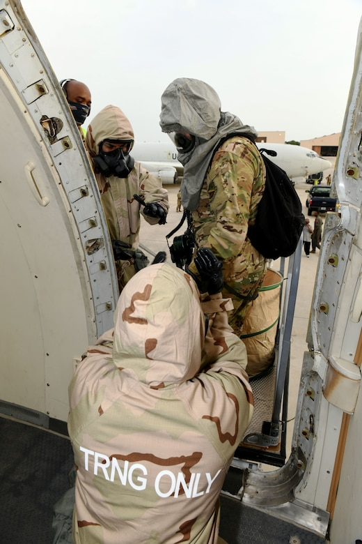 Photo shows Airmen helping someone in CBRNE gear maneuver onto an aircraft.