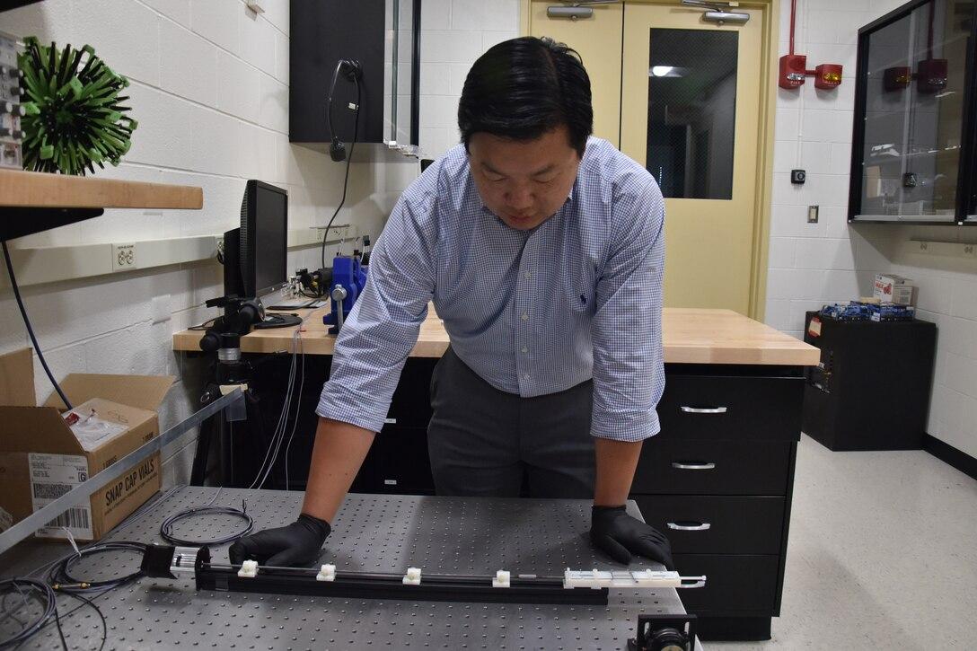 AFRL scientist, Dr. Vincent Chen, demonstrates the experimental setup used to trigger shape change in soft, magnetically responsive elastomers. (U.S. Air Force photo/Spencer Deer)