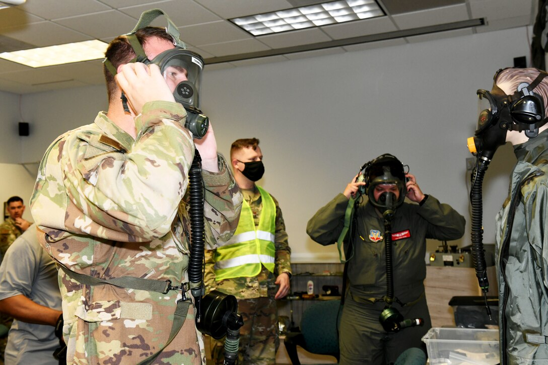 Photo shows two individuals putting on masks.