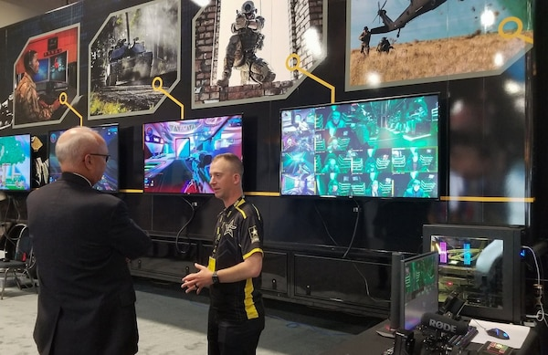 Sgt. 1st Class Christopher Jones (center), a member of the U.S. Army Recruiting Command's esports team, speaks in front of the team's semitrailer, which has gaming stations inside of it, during the Association of the U.S. Army's Annual Meeting and Exposition in Washington, D.C., Oct. 14, 2019. The command plans to create a cyber esports team and roll out autonomous recruiting operations, which will increase the mobility of recruiters with a larger social media presence.