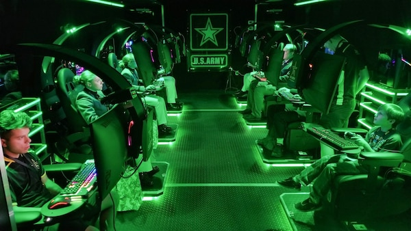 Visitors play video games inside a semitrailer belonging to the U.S. Army Recruiting Command's esports team during the Association of the U.S. Army's Annual Meeting and Exposition in Washington, D.C., Oct. 14, 2019. The command plans to create a cyber esports team and roll out autonomous recruiting operations, which will increase the mobility of recruiters with a larger social media presence.