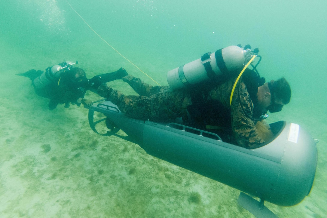 Two men use a propulsion device under water.