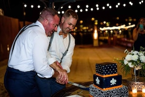 Two men stand next to each other at their wedding. Both are wearing white button-up shirts with suspenders and bowties. It's night in a festive atmosphere and they're slicing into their wedding cake.