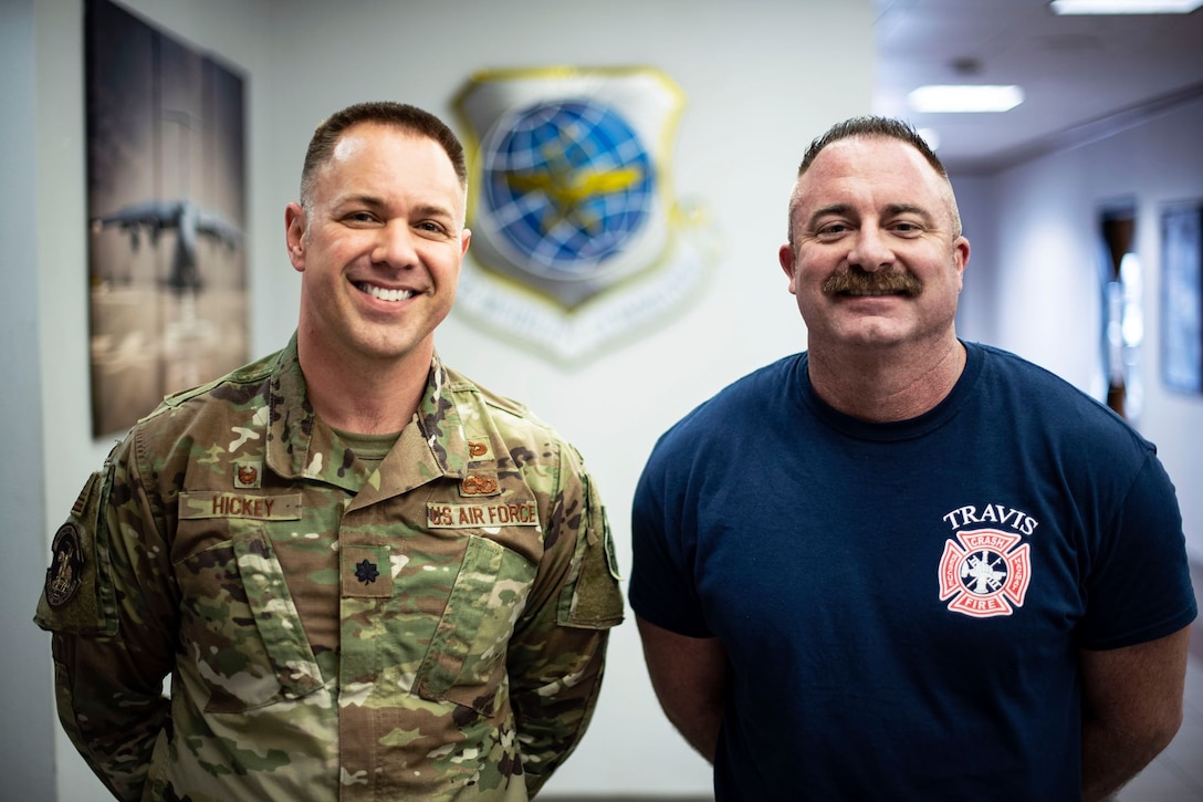 "Two men stand next to each other inside of a brightly-lit building. One wears a military uniform and one wears a tee shirt with ""Travis fire department"" on it. Both are smiling."