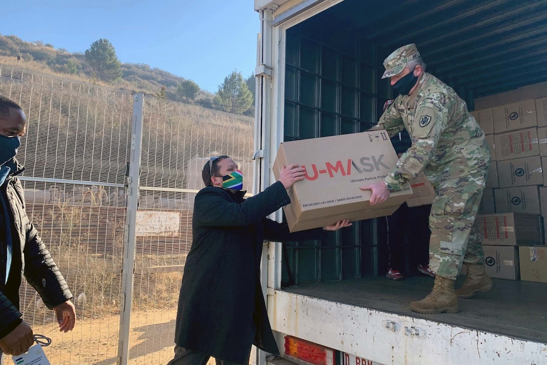 A soldier standing in a truck wearing a mask passes a box to someone standing on the ground and wearing a mask.
