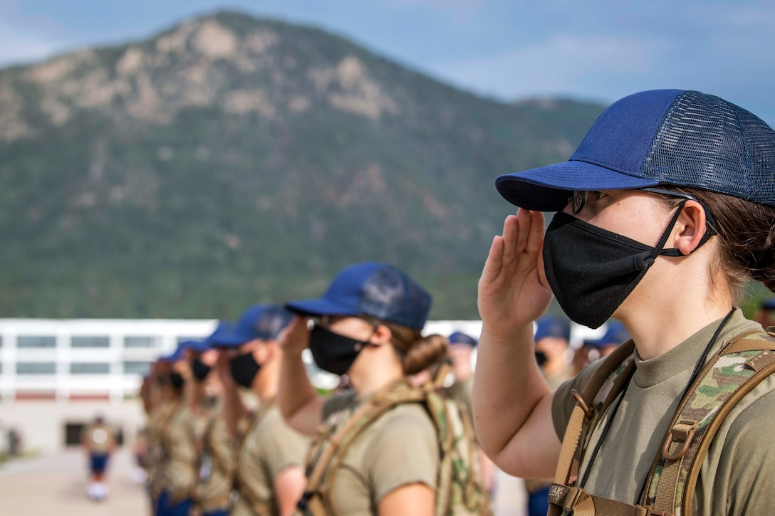 Women cadets wearing masks stand in formation and salute.