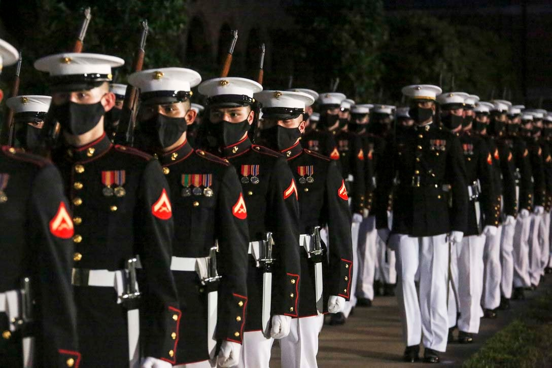Marines stand in formation while wearing masks.