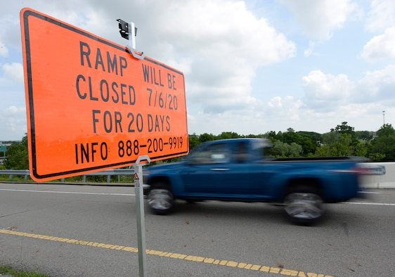 """A blue truck driving by a an orange rectangle sign that say """"RAMP WILL BE CLOSED 7/6/20 FOR 20 DAYS INFO 888-200-9919 in black letters."""