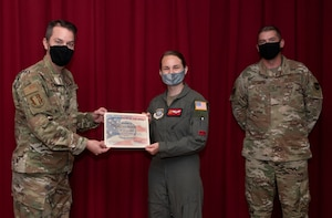 U.S. Air Force Col. Jeffrey Nelson, left, 60th Air Mobility Wing commander, and Chief Master Sgt. Stephen Scofield, right, 60th Maintenance Squadron squadron superintendent, recognize Airman 1st Class Sara Marinelli, 21st Airlift Squadron loadmaster, as the Warrior of the Week, June 23, 2020, at Travis Air Force Base, California. The program recognizes outstanding Airmen who have made significant contributions to their unit. (U.S. Air Force photo by Heide Couch)