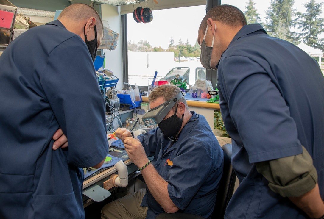 U.S. Air Force Chief Master Sgt. Derek Crowder, left, 60th Air Mobility Wing command chief, and Col. Zachery Jiron, 60th AMW vice commander, right, watch Robert Silva, center, 60th Dental Squadron dental laboratory technician create a wax mold for a dental crown during Leadership Rounds June 26, 2020, at David Grant USAF Medical Center, Travis Air Force Base, California. The Leadership Rounds program provides 60th AMW leadership an opportunity to interact with Airmen and get a detailed view of each mission performed at Travis AFB.  (U.S. Air Force photo by Heide Couch)