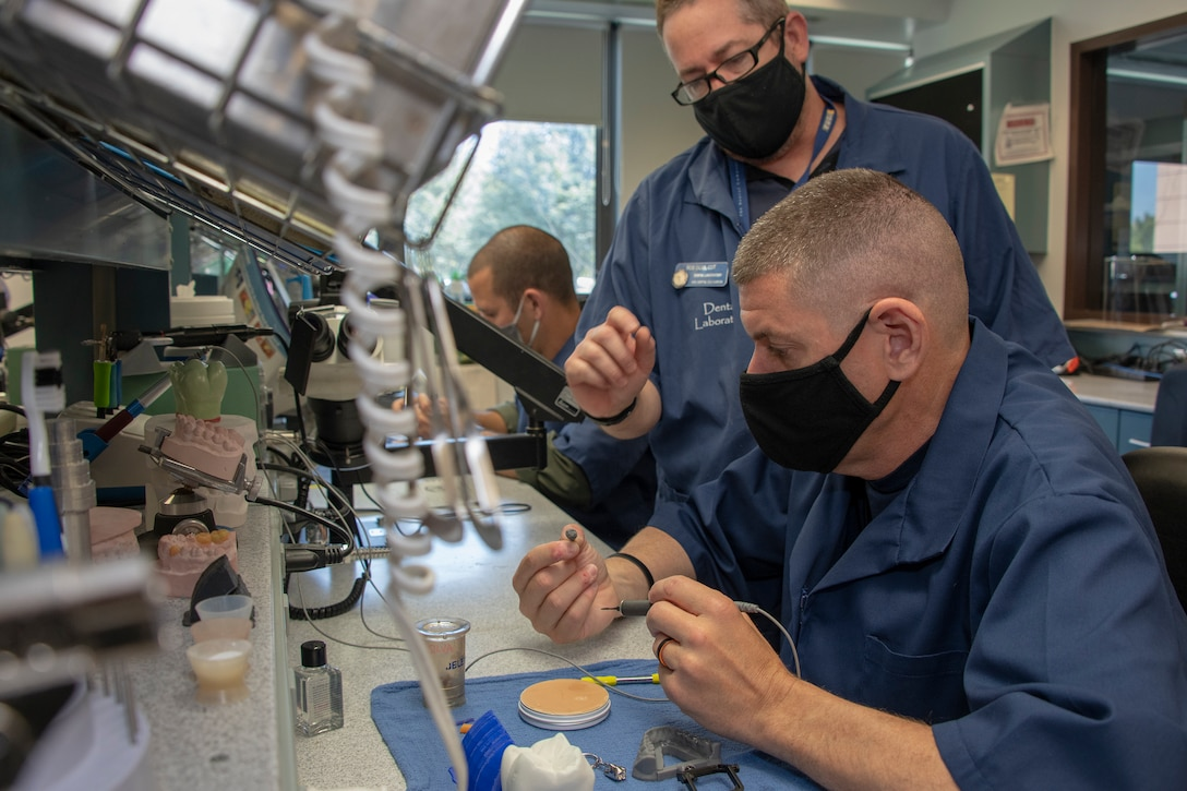 U.S. Air Force Chief Master Sgt. Derek Crowder, right, 60th Air Mobility Wing command chief, uses wax to create a dental crown mold while Robert Silva, 60th Dental Squadron dental laboratory technician watches during Leadership Rounds June 26, 2020, at David Grant USAF Medical Center, Travis Air Force Base, California. The Leadership Rounds program provides 60th AMW leadership an opportunity to interact with Airmen and get a detailed view of each mission performed at Travis AFB.  (U.S. Air Force photo by Heide Couch)