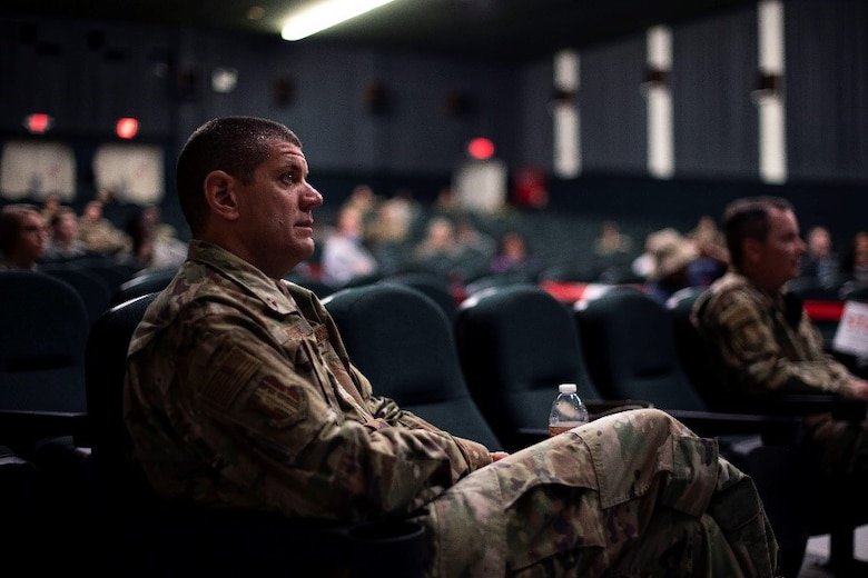 A man in a military uniform sits in a theater with others in attendance while he looks on at someone off screen.