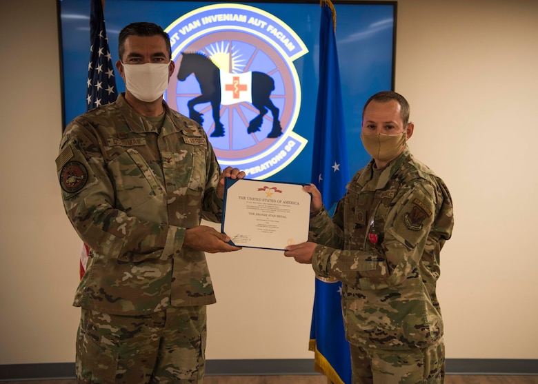U.S. Air Force Col. Richard Goodman, 366th Fighter Wing commander, presents a Bronze Star to Master Sgt. Mark Hurd, 366th Healthcare Operations Squadron medical logistics flight chief, June 24, 2020, at Mountain Home Air Force Base, Idaho. Hurd completed 72 outside-the-wire advising missions while exposed to significant danger including indirect fire, insider threats and direct fire engagements.
