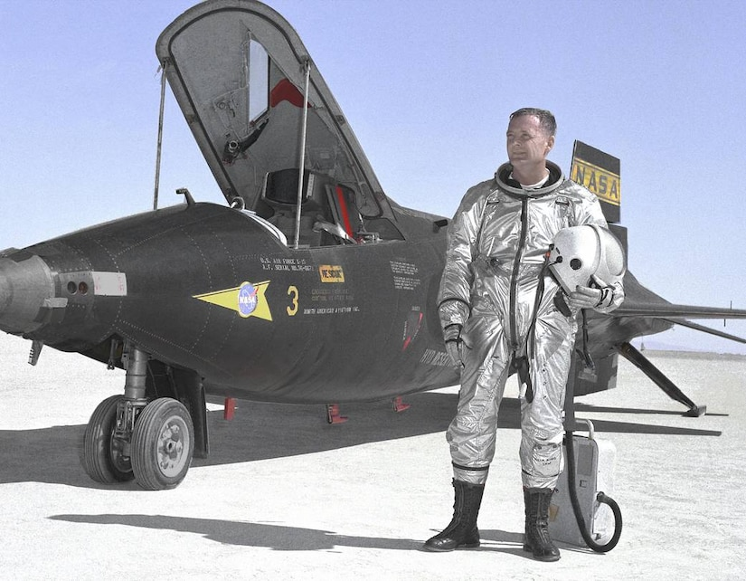A man in a silver suit stands in front of a military-style research aircraft.