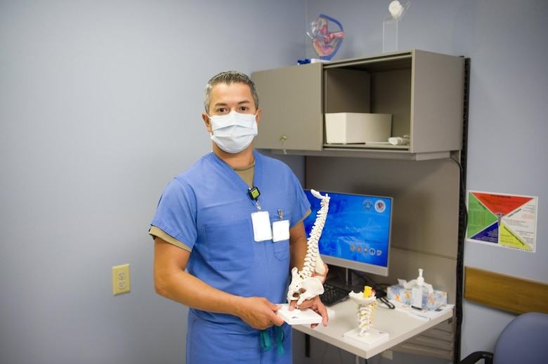 Capt. Juan Moreno, 15th Medical Group Active Duty Clinic physician assistant, holds a model of the human spine, to bring awareness to the musculoskeletal problems men face at Joint Base Pearl Harbor-Hickam, Hawaii, June 25, 2020. The 15th MDG provides both in-person and virtual medical appointments to Airmen during the COVID-19 pandemic and can assist with men's health issues. (U.S. Air Force Illustration by 2nd Lt. Benjamin Aronson)