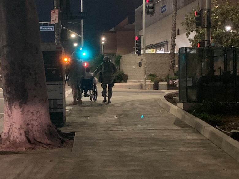 U.S. Air National Guard Tech. Sgt. Omar Godoy and Master Sgt. Jordan Kennedy from the California Air National Guard's 146th Airlift Wing's Security Forces Squadron, assist with transporting a elderly pedestrian by pushing his wheelchair up Temple Ave in Los Angeles, California. June 1, 2019. Courtesy photo by California Military Department.