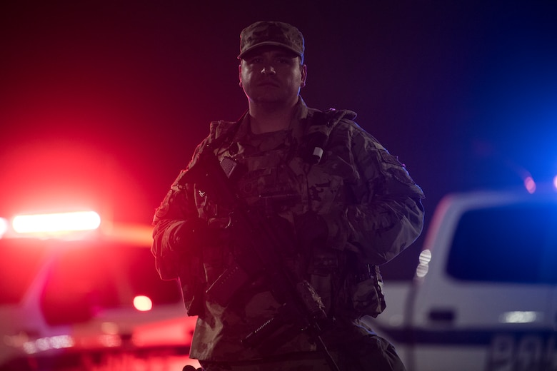A photo of a U.S. Air National Guard Security Forces defender standing in front of two police vehicles that are flashing red and blue lights.