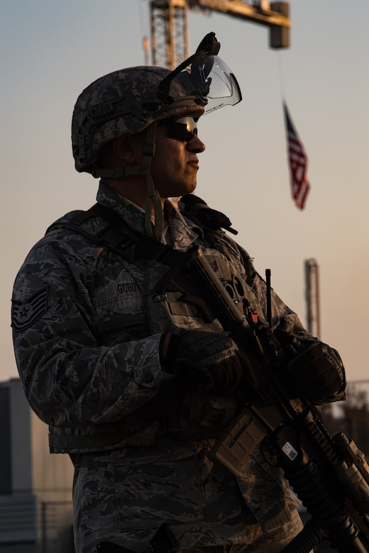 A California Air National Guard Security Forces defender stares into the sunset as the outline shape of his body silhouettes from the setting sun. A U.S. Flag hangs from a construction crane behind him.