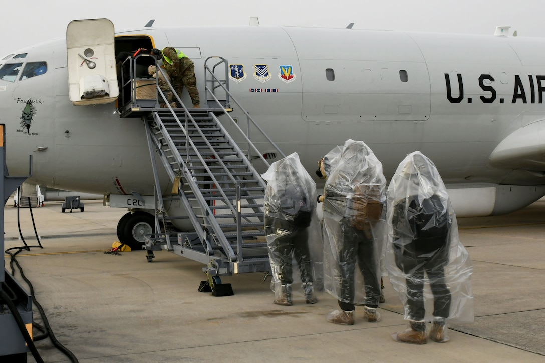 Photo shows Airmen lined up at foot of stairs waiting to board an aircraft.