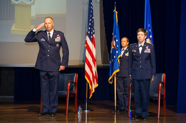 Col. Chad Hartman (left), commander of the Air Force Technical Applications Center, Patrick AFB, Fla., salutes and relinquishes command during a Change of Command ceremony June 30, 2020 as his replacement, Col. Katharine Barber (right) stands at attention.  Also pictured is guidon bearer Chief Master Sgt. Amy Long (center), AFTAC's command chief.  (U.S. Air Force photo by Amanda Ryrholm)