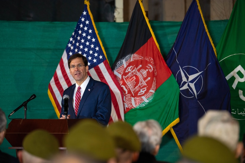 Defense Secretary Dr. Mark T. Esper speaks at a lectern with U.S., Afghan and NATO flags behind him.