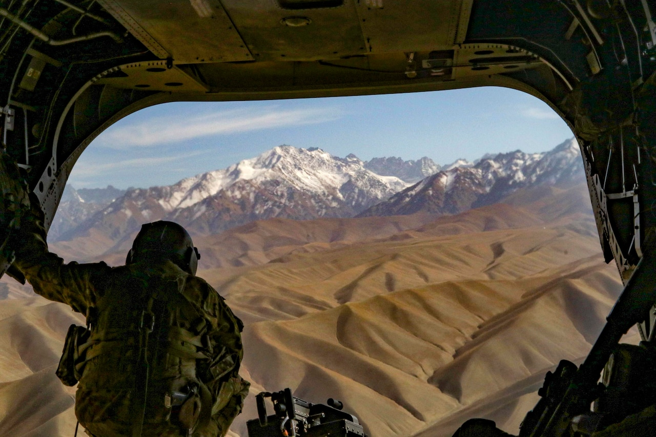 A soldier crouches and looks out the back of a helicopter flying near snow-capped mountains.