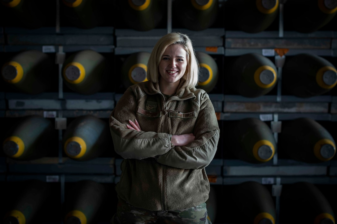 U.S. Air Force Airman 1st Class Autumn Gregory, 86th Munitions Squadron munitions stockpile management technician, poses for a photo in front of a stockpile of munitions at Ramstein Air Base, Germany, Feb. 6, 2020. The 86th Munitions Squadron received more than 200 crates of various munitions and inert components to be distributed to combatant commands in the region. (U.S. Air Force photo by Staff Sgt. Devin Nothstine)