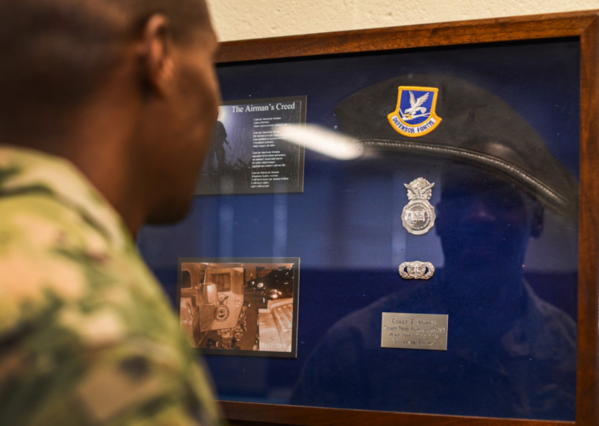 Tech. Sgt. Corey Nowell, noncommissioned officer in charge of movement support at the Joint Personal Property Shipping Office Northeast, is reflected in his security forces shadow box at Hanscom Air Force Base, Mass., Feb. 21, 2020. Nowell enlisted in the Air Force at 18 years old as a security forces defender but retrained as a traffic manager following a car accident that resulted in a level-2 concussion. (U.S. Air Force photo by Mark Herlihy)
