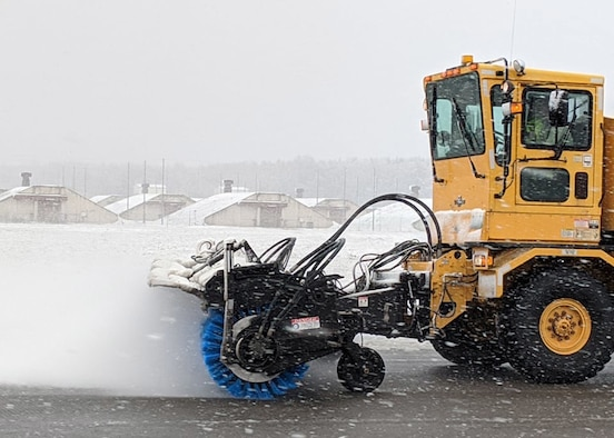 An Oshkosh Snow Broom snow removal vehicle sweeps a runway clear of snow during winter weather on Ramstein Air Base, Germany, Feb. 27, 2020.