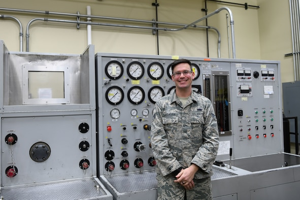 A man stands in front of a machine.