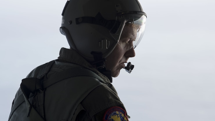 A loadmaster prepares to deploy illumination flares from the ramp of an aircraft.