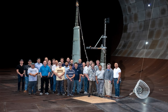The team responsible for the testing of the integrated Actively Stabilized Refueling Drogue System and Optical Reference System stands with the tested hose and drogue system in the 40- by 80-foot wind tunnel at the Arnold Engineering Development Complex National Full-Scale Aerodynamics Complex, located in the NASA Ames Research Center at Moffett Field in Mountain View, California. The NFAC test team consisted of both Department of Defense and Test Operations and Sustainment contract employees from National Aerospace Solutions. The team included researchers, engineers, technicians and mechanics. (Courtesy photo)