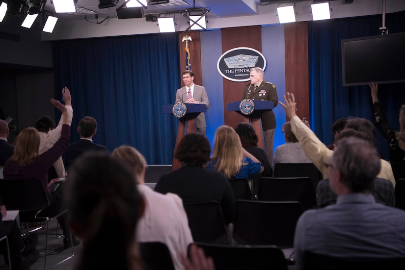 Reporters raise their hands as Defense Secretary Dr. Mark T. Esper and Army Gen. Mark A. Milley stand at lecterns.