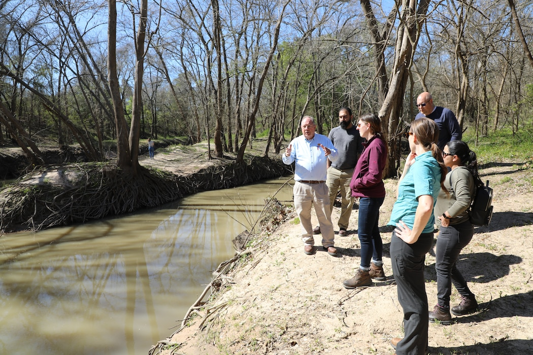 """HOUSTON (Feb. 28, 2020) –Richard Long, natural resource management specialist with the Houston Project Office of the U.S. Army Corps of Engineers Galveston District, discusses the confluence of Buffalo Bayou and Langham Creek downstream of Addicks and Barker dams with members of the Water Management Team of the Galveston District.   Sarah Delavan, chief of the Water Management Section, said """"it is important for the team to have a clear understanding of how Addicks and Barker dams and reservoirs function from the top of the watershed to the Houston Ship Channel. What better way to obtain that"""