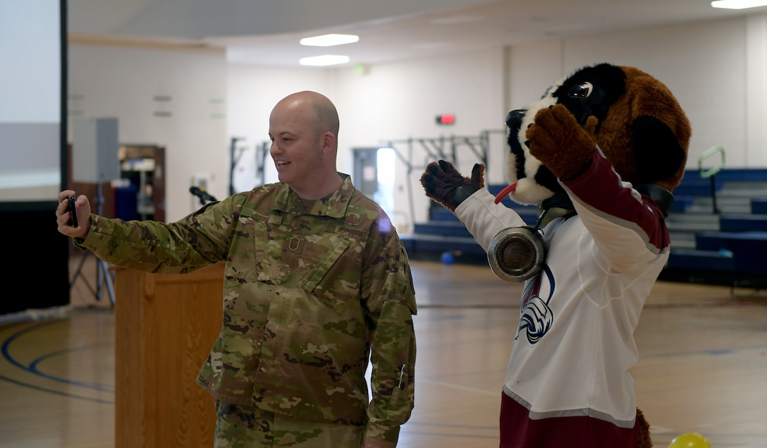 Senior Master Sgt. Jeff Stone, 460th Security Forces Squadron first sergeant, takes a selfie with the Avalanche Hockey Team mascot prior to the start of the Annual Awards Ceremony at Buckley Air Force Base, Colo., Feb. 28, 2020.