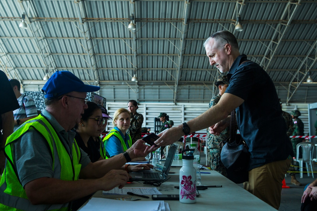A Thai government official receives a simulated noncombatant evacuee's passport during a noncombatant evacuation operation as part of Exercise Cobra Gold 2020 at Utapao, Kingdom of Thailand, Feb. 29.