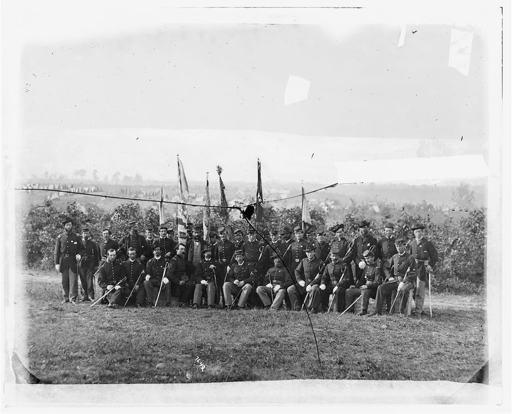 A unit of men in Civil War garb pose for a photo in front of a crop field.