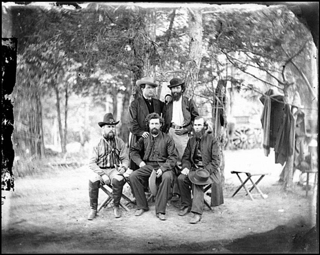 Five Civil War-era men, two standing and three sitting, pose for a black-and-white photo in a wooded area. Clothes can be seen hanging from tree limbs nearby.