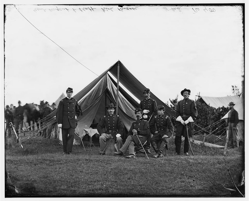 Six Civil War officers, three sitting and three standing, pose for a black-and-white photo in a field that has a pitched tent behind them.