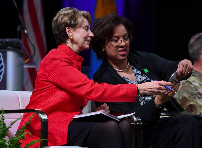 Secretary of the Air Force Barbara Barrett and Toni Townes-Whitley, U.S. Regulated Industries president, look at a magnetic coaster created by U.S. Air Force Tech. Sgt. Daniel Caban, 1st Aircraft Maintenance Squadron crew chief, during the Spark Tank competition in Orlando, Florida, Feb. 28, 2020.