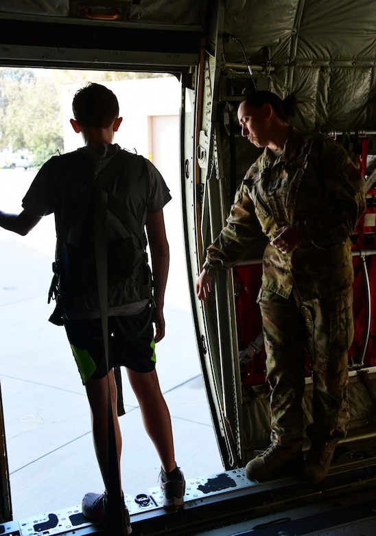 Tech. Sgt. Kristine Thomas helps a student lean out a door on the back of a C-130 J aircraft.